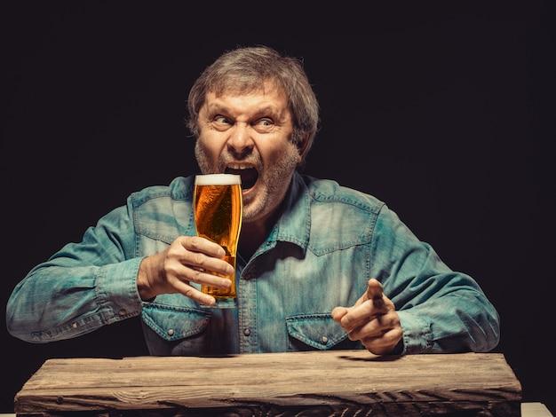 O homem gritando em camisa jeans com copo de cerveja Foto gratuita