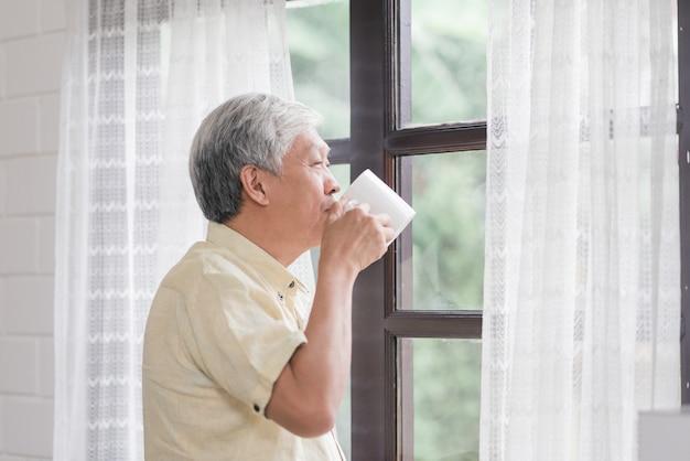 O homem idoso asiático feliz que sorri e que bebe uma xícara de café ou um chá perto da janela na sala de visitas, homem superior de ásia abre as cortinas e relaxa na manhã. Foto gratuita