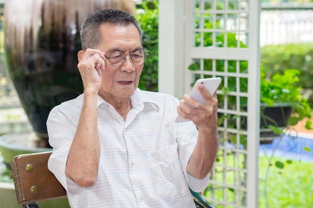 O homem idoso asiático idoso feliz guarda vidros do olho e olhando o smartphone em exterior. Foto Premium