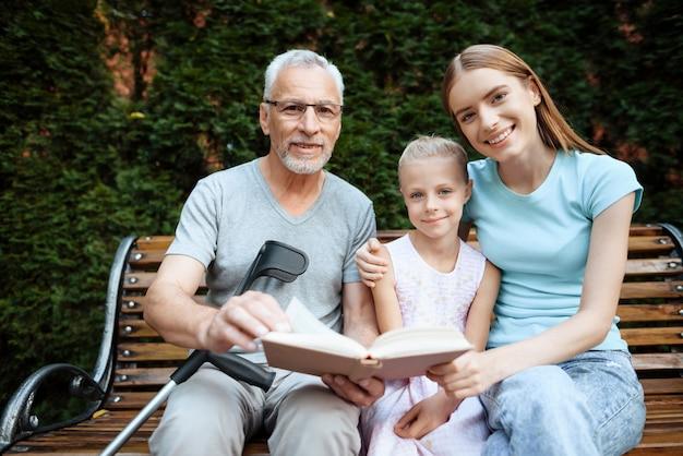 O homem idoso com seus parentes senta-se em um banco. Foto Premium