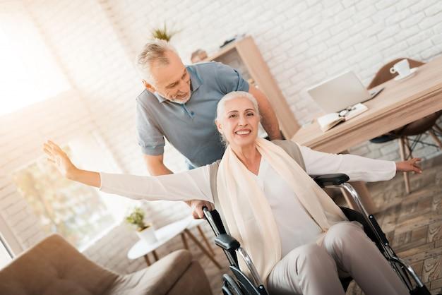 O homem idoso cuida da mulher madura em cadeira de rodas. Foto Premium