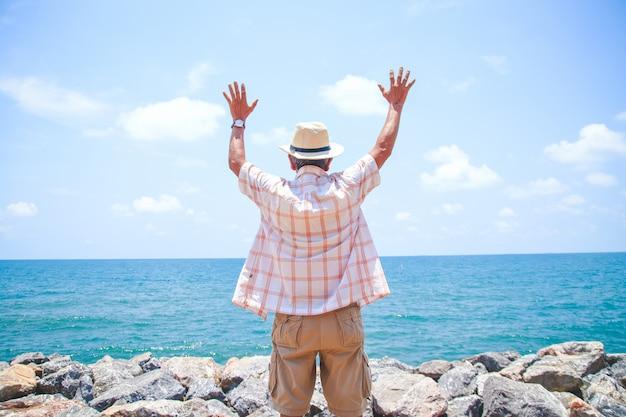 O homem idoso usava um chapéu, virou as costas, deixando-o levantar as mãos com alegria ao vir para o mar. Foto Premium