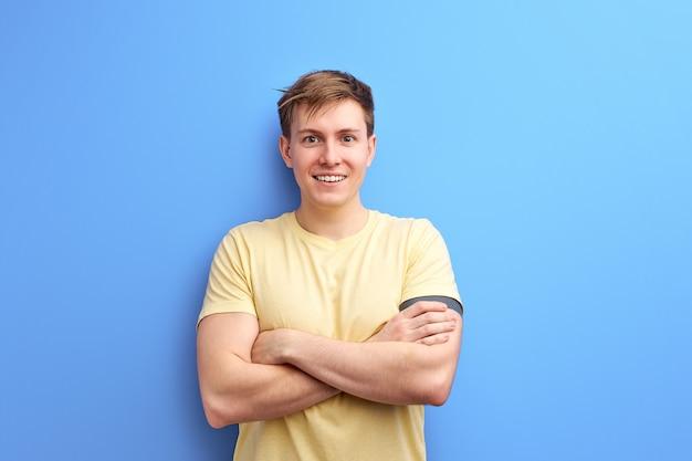 O homem inspirado na roupa de camiseta casual está sorrindo com os braços cruzados. isolado sobre o fundo azul do estúdio. estilo de vida, pessoas, conceito de emoções humanas Foto Premium