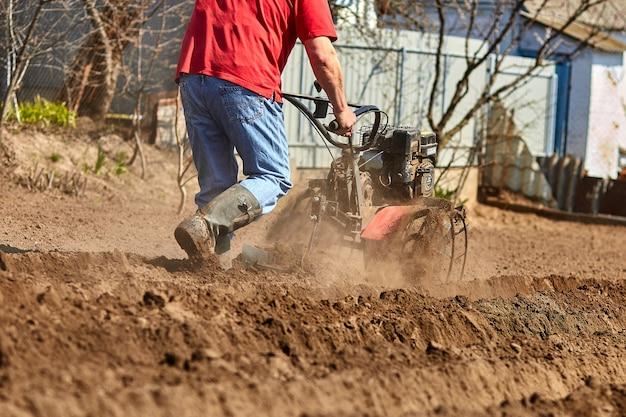 O homem jardineiro cultiva o solo do solo com um trator de cana ou rototiller, um cutivador, uma máquina de plantio Foto Premium