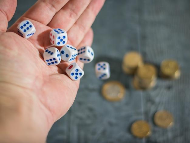 O homem joga os dados do jogo em cima da mesa com moedas. cubos de dinheiro e jogos. Foto Premium