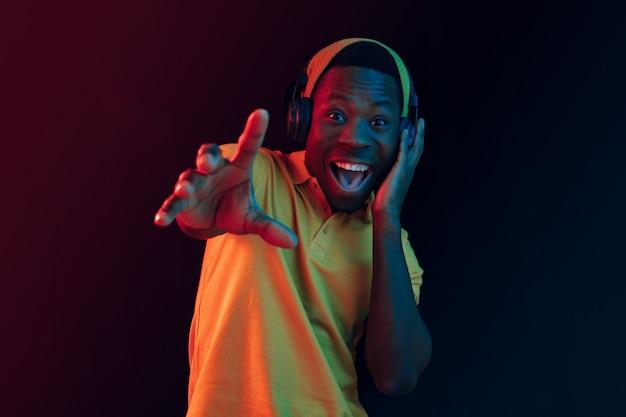 O homem jovem bonito feliz hipster ouvindo música com fones de ouvido no estúdio preto com luzes de néon. discoteca, boate, estilo hip hop, emoções positivas, expressão facial, conceito de dança Foto gratuita