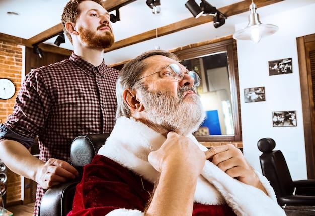 O homem mais velho com fantasia de papai noel fazendo a barba de seu mestre pessoal na barbearia antes do natal Foto gratuita