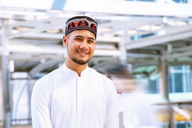O homem muçulmano está de pé na cidade. ele está sorrindo. Foto Premium