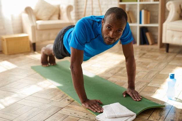O homem negro atlético executa a prancha na esteira em casa. Foto Premium