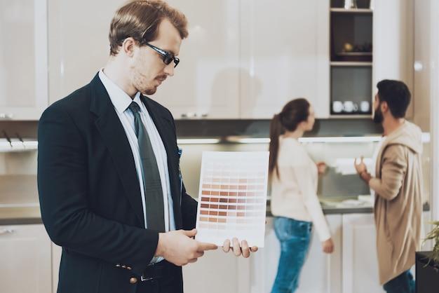 O homem no terno está mostrando amostras de cores na loja da cozinha. Foto Premium