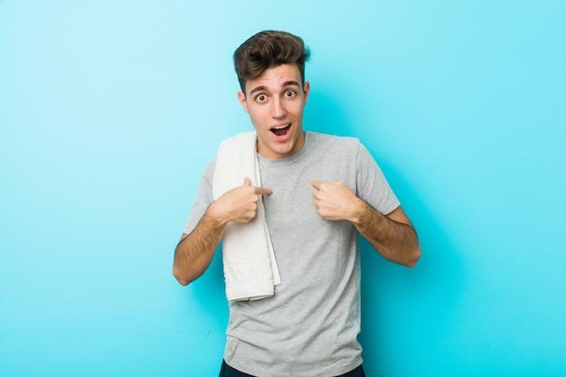 O homem novo do adolescente da aptidão surpreendeu apontar com o dedo, sorrindo amplamente. Foto Premium
