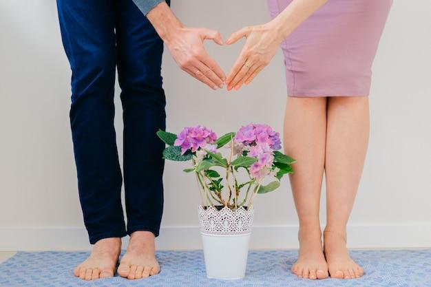 O homem novo e a menina entrelaçaram as mãos e o coração assina sobre o potenciômetro de flores. Foto Premium