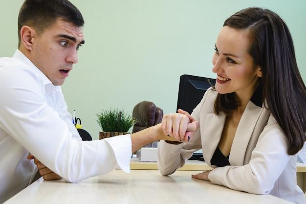 O homem novo e a mulher lutam em suas mãos na mesa no escritório por um lugar chefe, cabeça Foto Premium