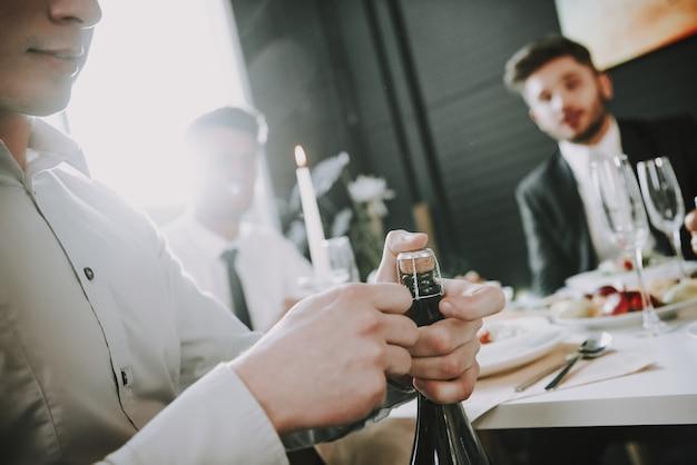 O homem novo está abrindo o champanhe. mesa de jantar. Foto Premium