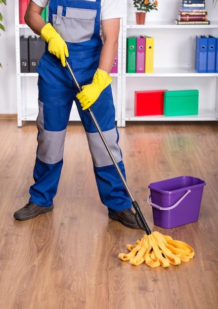 O homem novo no uniforme azul está limpando o assoalho. Foto Premium