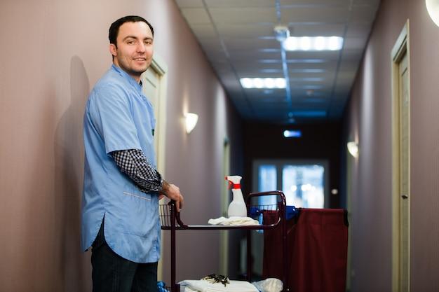 O homem que está no pessoal da equipe de limpeza do hotel está sorrindo com um aspirador de pó no processo de limpeza dos quartos do hotel e entrega de serviço de primeira qualidade aos hóspedes. Foto Premium