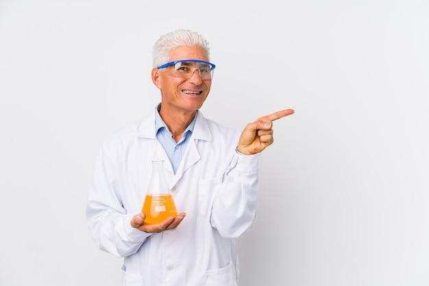O homem químico maduro isolou o sorriso e apontar de lado, mostrando algo no espaço em branco. Foto Premium