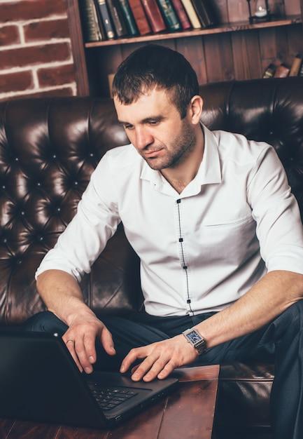 O homem rico senta-se em um sofá de couro atrás de um portátil seu escritório. Foto Premium