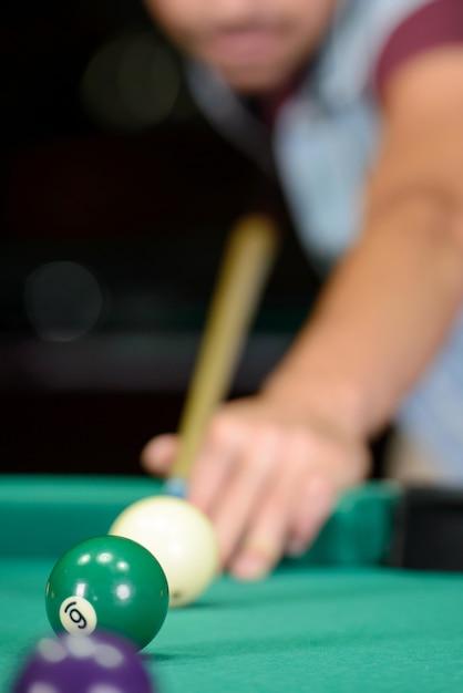 O homem segura a deixa e acerta as bolas de bilhar. Foto Premium