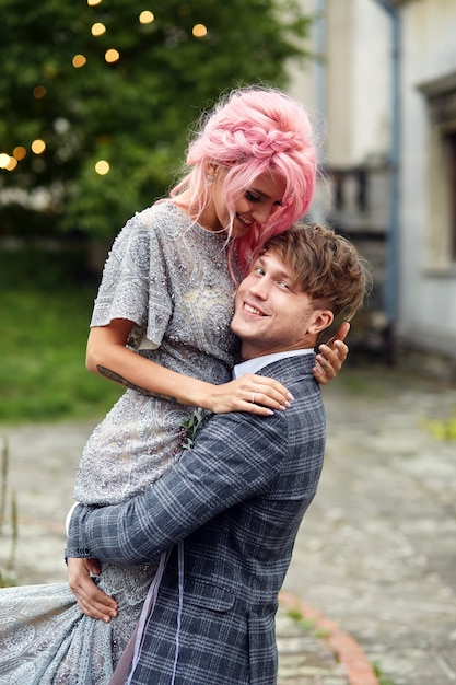 O homem segura a mulher com cabelo rosa de pé contra o vento Foto gratuita