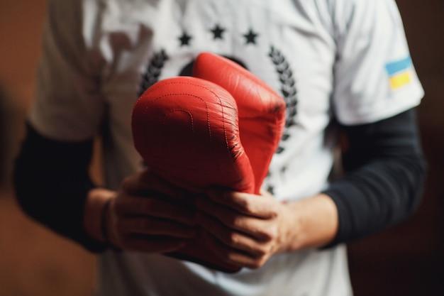 O homem segura luvas de boxe nas mãos Foto gratuita