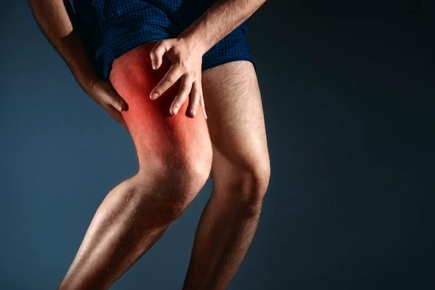 O homem segura o joelho, a dor no joelho Foto Premium