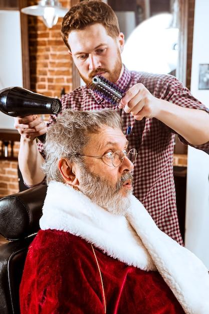 O homem sênior com fantasia de papai noel fazendo a barba de seu mestre pessoal na barbearia antes do natal Foto gratuita