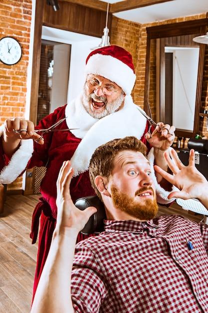 O homem sênior com fantasia de papai noel trabalhando como mestre pessoal com uma tesoura na barbearia antes do natal Foto gratuita