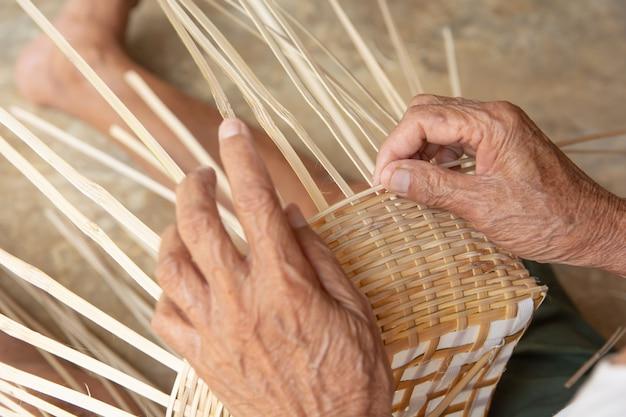 O homem sênior entrega manualmente o bambu de tecelagem. Foto Premium
