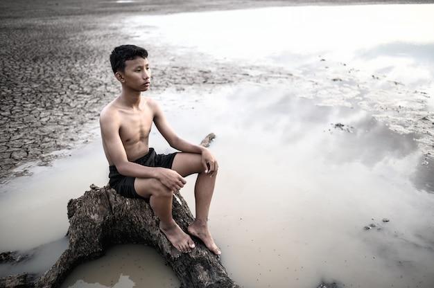 O homem sentou-se na base da árvore, colocou as mãos nos joelhos e olhou para a frente. Foto gratuita