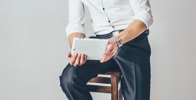 O homem tem um tablet nas mãos. ele se senta em uma cadeira vestido com uma camisa branca e calça chique Foto Premium