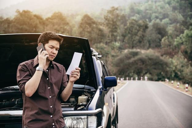 O homem tenta consertar um problema de motor de carro em uma estrada local Foto gratuita