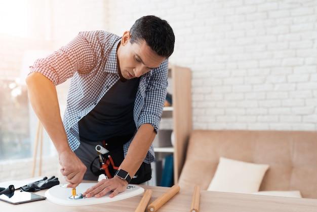O homem tenta dobrar sua mesa de café e fezes. Foto Premium
