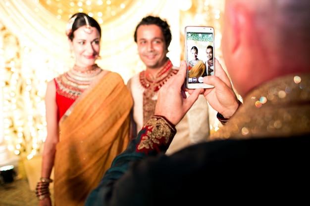 O homem tira foto do casal de casamento hindu no smartphone Foto gratuita