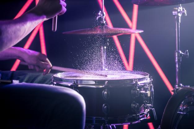 O homem toca bateria, no fundo de luzes coloridas Foto gratuita
