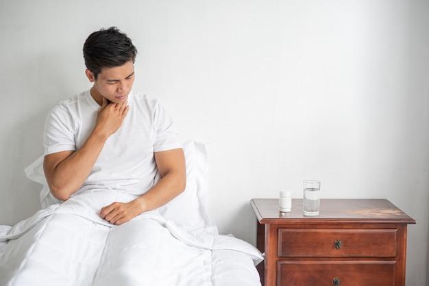 O homem tossiu, tapou a boca com a mão e sentou-se na cama. Foto gratuita