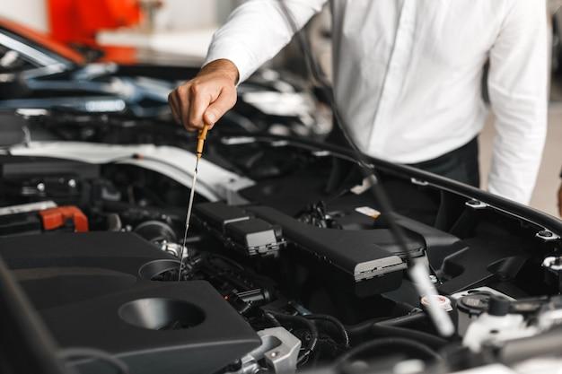 O homem verifica a presença de óleo no carro. mão masculina de close-up Foto Premium