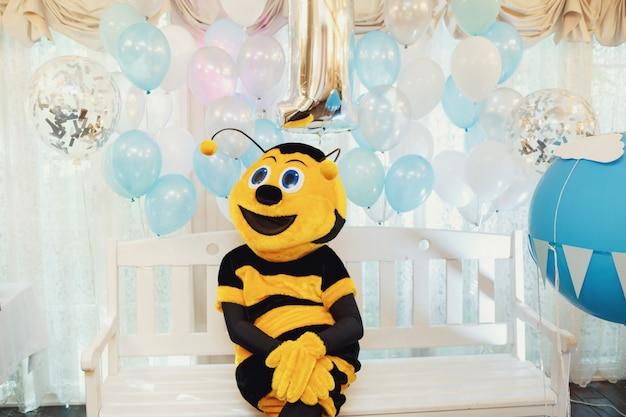O homem vestido como uma abelha senta no banco Foto gratuita
