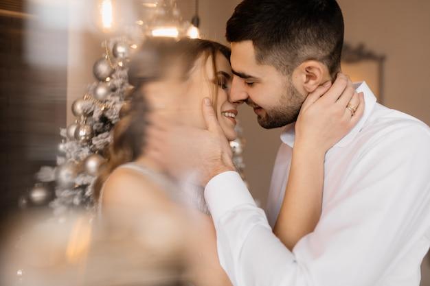 O homem vestido extravagante e a mulher no vestido de prata abraçam-se mutuamente em pé antes de uma árvore de natal Foto gratuita
