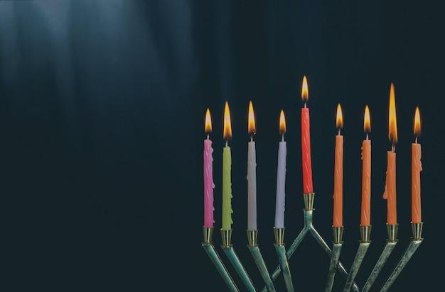 O iluminado de velas de hanukkah em menorah em fundo azul Foto Premium