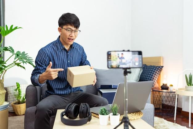 O influenciador de mídia social ou blogueiro apresenta e analisa a gravação ou streaming de vlog sobre o produto usando smartphone no tripé para canal de mídia social criando conceito de transmissão ao vivo. Foto Premium