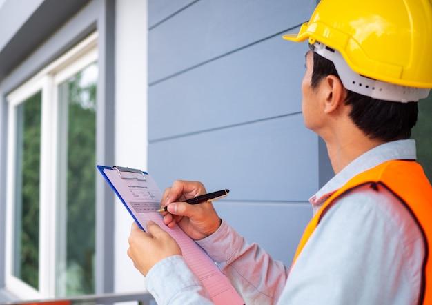 O inspetor ou engenheiro está verificando a estrutura do edifício e os requisitos da pintura de parede. Foto Premium