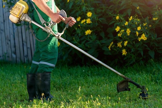 O jardineiro corta a grama com um cortador de grama. Foto Premium