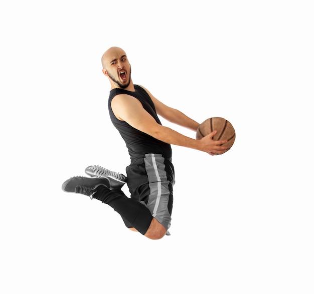 O jogador de basquete faz uma enterrada no branco. o jogador de basquete faz enterrada. Foto Premium