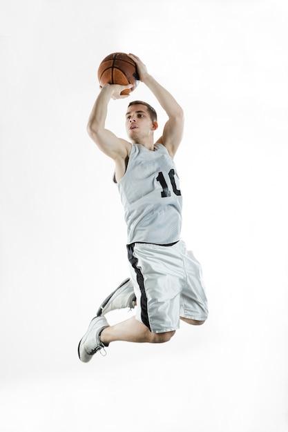 O jogador de basquetebol salta acrobaticamente Foto gratuita