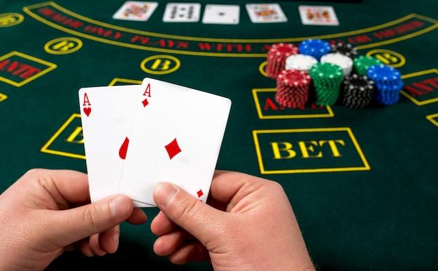 O jogador de pôquer tem cartas. visão em primeira pessoa. dois ases, uma combinação vencedora. mãos masculinas Foto Premium
