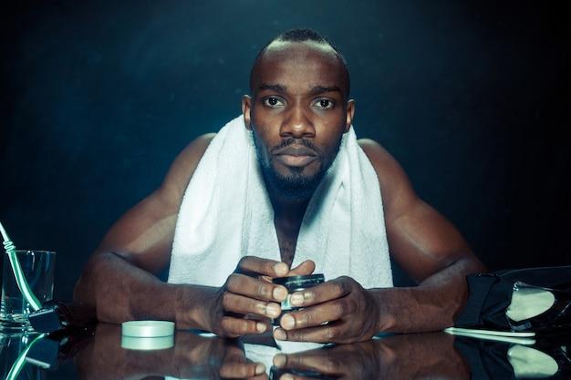 O jovem africano no quarto, sentado em frente ao espelho, depois de coçar a barba em casa. conceito de emoções humanas. conceitos de creme pós-barba Foto gratuita