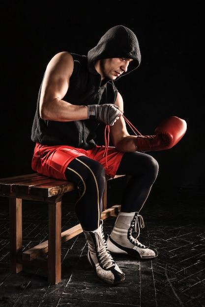 O jovem atleta masculino de kickboxing sentado e amarrando uma luva em um preto Foto gratuita