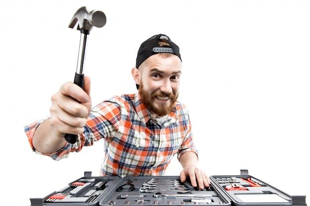 O jovem barbudo segura uma ferramenta de reparo Foto Premium