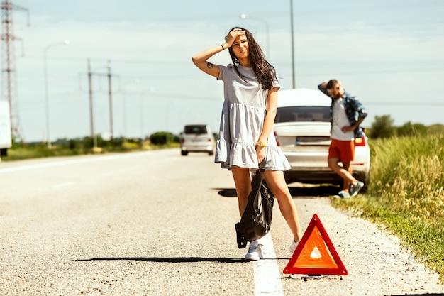 O jovem casal quebrou o carro durante uma viagem para descansar. eles estão tentando parar outros motoristas e pedir ajuda ou pedir carona. relacionamento, problemas na estrada, férias. Foto gratuita